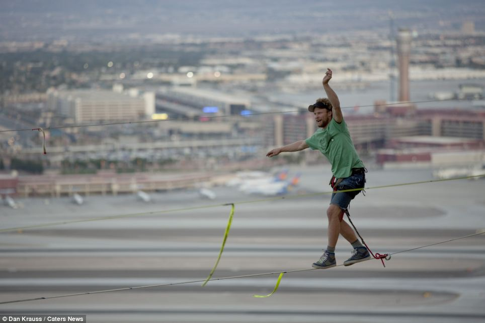 Andy Lewis holds one arm to the side and one aloft as he slowly works his way along the line. His walk broke the world record for longest distance walked on a slackline in an urban environment
