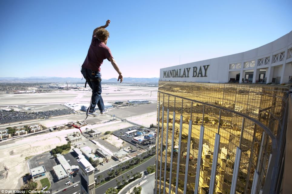 Fearless Andy Lewis adjusts his arms and thrusts his hips to the left as he balances precariously on a one-inch wide line hundreds of feet above the ground in Las Vegas. Cars and trees look like tiny models from the lofty position above the city's airport