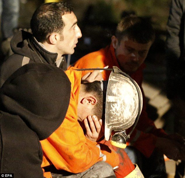 Heartbroken: Miners cry after they retrieved a dead colleague from the mine
