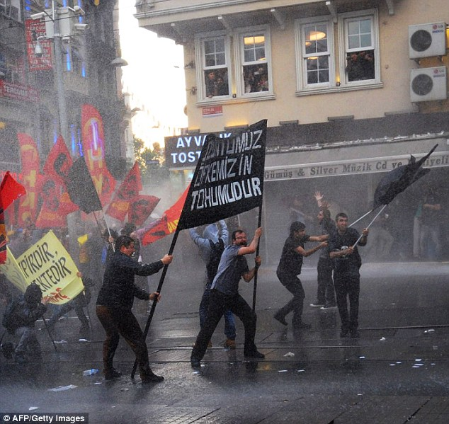Protesters holds flags and banners as Turkish riot police use water cannon to combat their demonstration