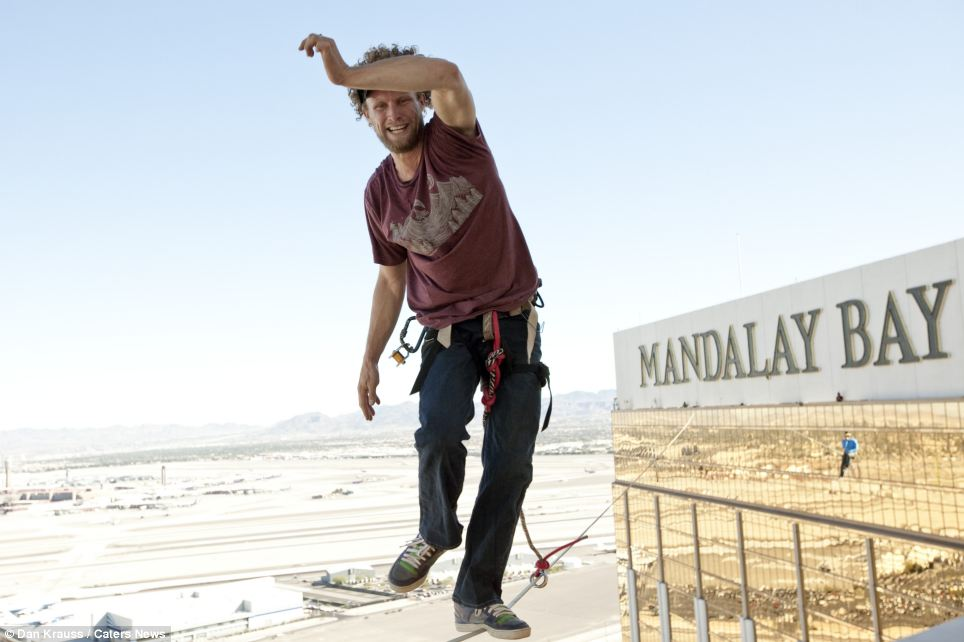 Andy Lewis concentrates and almost manages a smile as he balances with one foot across the one-inch line. Despite the buzzing drones, constant planes taking off at McCarran International Airport, pictured below, and swirling wind at 480ft, he was able to make it across the line without falling on his third attempt