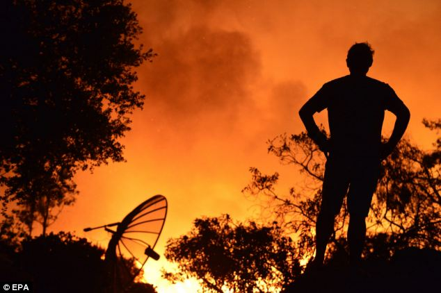 A San Marcos resident who did not evacuate watching flames near his home, in the San Diego county yesterday. A spate of wildfires in southern California burned at least 30 homes and even forced the evacuation of the San Onofre nuclear power plant.