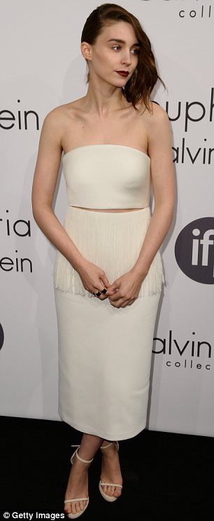 Pale and interesting: Rooney Mara chose a cropped white top and long skirt with a fringed waist to hit the black carpet