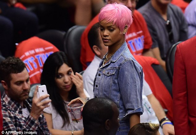 Cover up: Rihanna soon covered up with a denim jacket over her tiny white vest but still drew attention