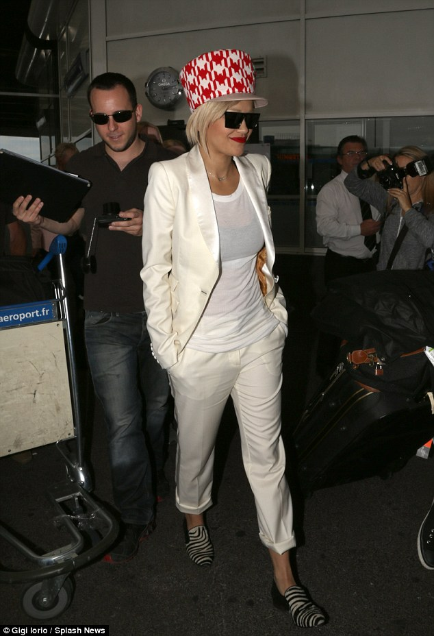 Hats the way: Rita Ora debuts her hair-raising cap in Nice on her way t9o Cannes