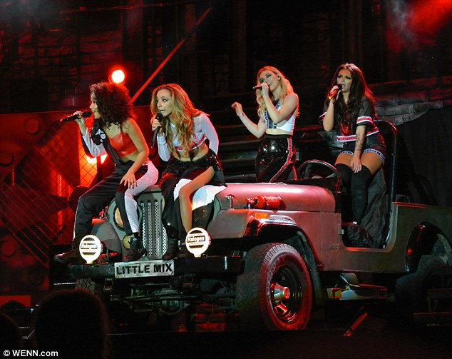 Drive by: They perched on the Little Mix army tank which remained on stage for the show