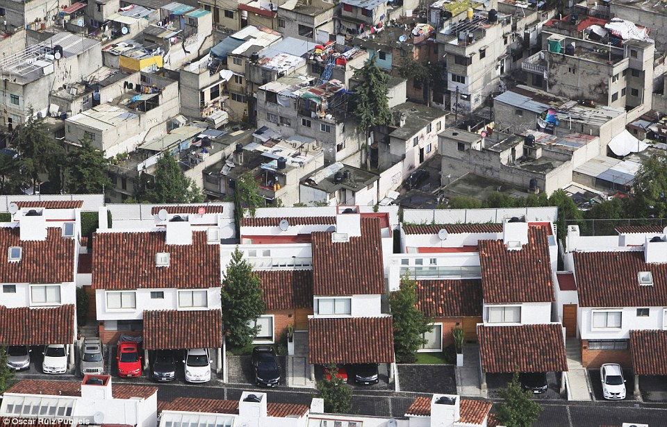 Tumbeldown: The smart roofs and garages of the homes in the foreground are a far cry from the corrugated roofs and makeshift washing lines of the poorer homes