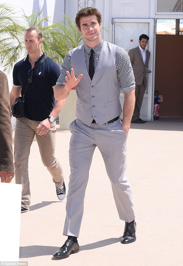 Off he goes: Liam waves to fans as he leaves Agora in Cannes