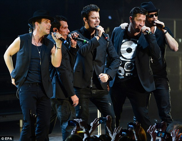 Have barely aged: Joey McIntyre, Danny Wood, Jordan Knight, Jonathan Knight, and Wahlberg looked soulful while huddling together