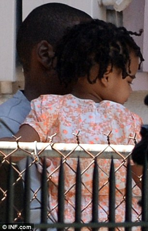 Cuddles for daddy: Little Blue looked cute as a button in an orange and white dress