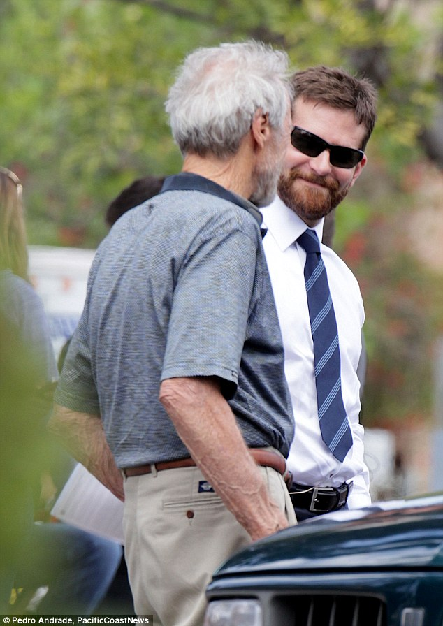 Working hard: Bradley sported a scruffy beard and sunglasses while engaged with his director