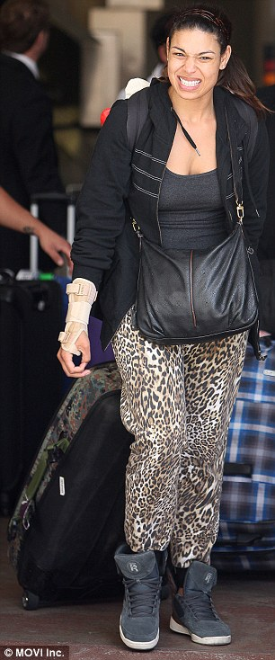 Keeping it real: The star showed no signs of diva demands as she wheeled her own colourful suitcase while also laden down by a black handbag and a large white Hello Kitty backpack