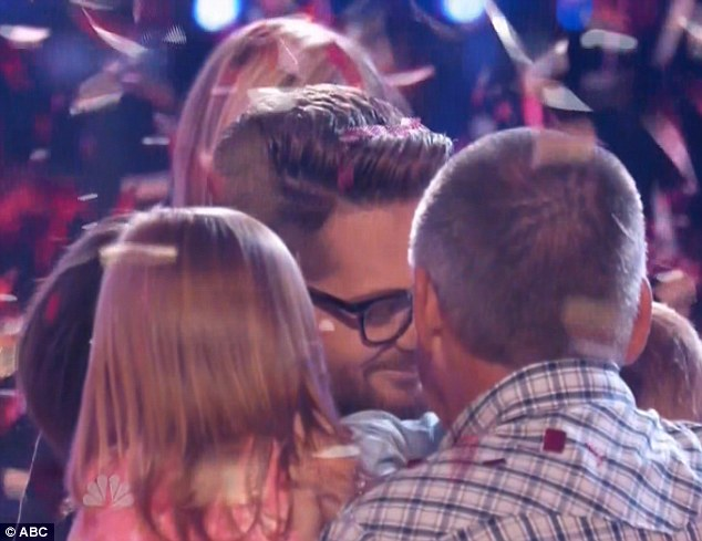 Popular winner: The 38-year-old father-of-three was rushed by family members as he enjoyed his moment