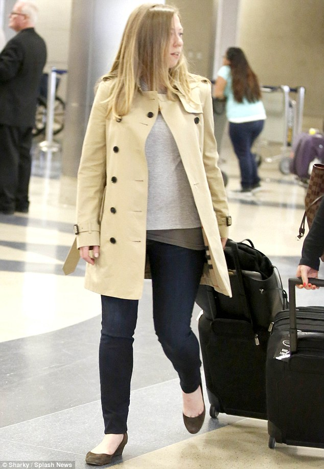 Looking effortless in a Burberry trench coast, jeans and ballet flats, the 34-year-old showed off her growing baby bump as she left the terminal