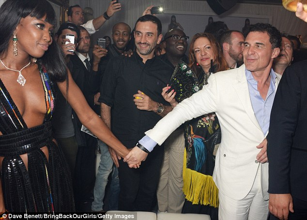 Adoring entourage: Cell phone cameras flashed as Campbell clasped hands with hotelier André Balazs before Givenchy's Riccardo Tisci (M) and W Magazine's Edward Enninful (wearing glasses)