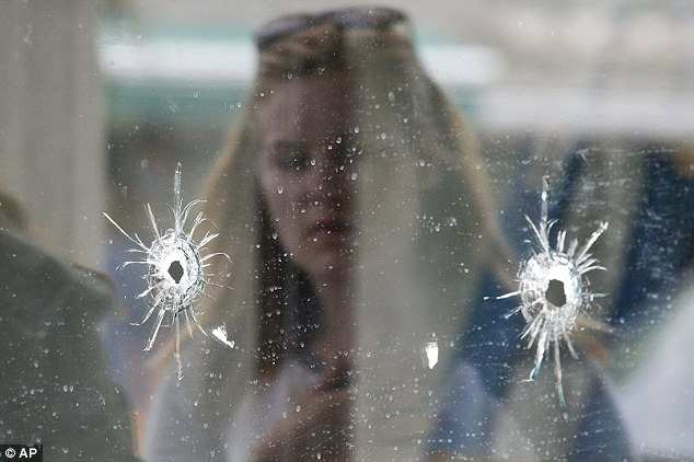 Shattered: A woman looks at the bullet holes on the window of IV Deli Mark where Friday night's mass shooting took place