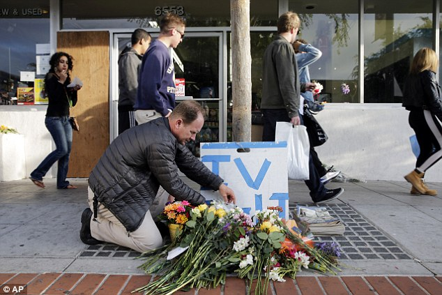 Stephen Nichols arranges flowers left in front of IV Deli Mart, where part of Friday night's mass shooting took place