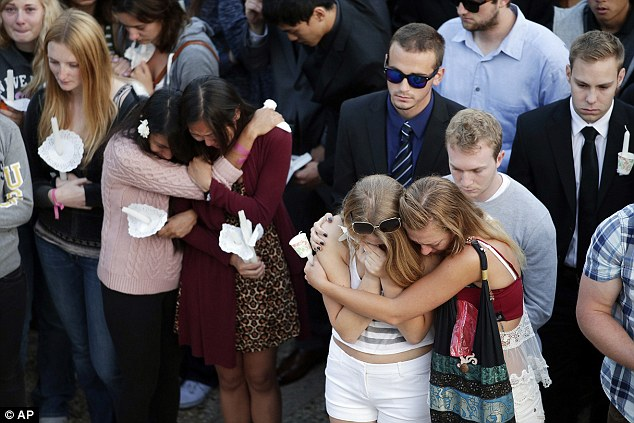 Overcome with sorrow: Students weeps and comfort each other while honoring their fallen classmates