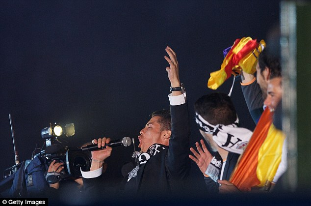 Leading the celebrations: Cristiano Ronaldo sings into a microphone on the open top bus