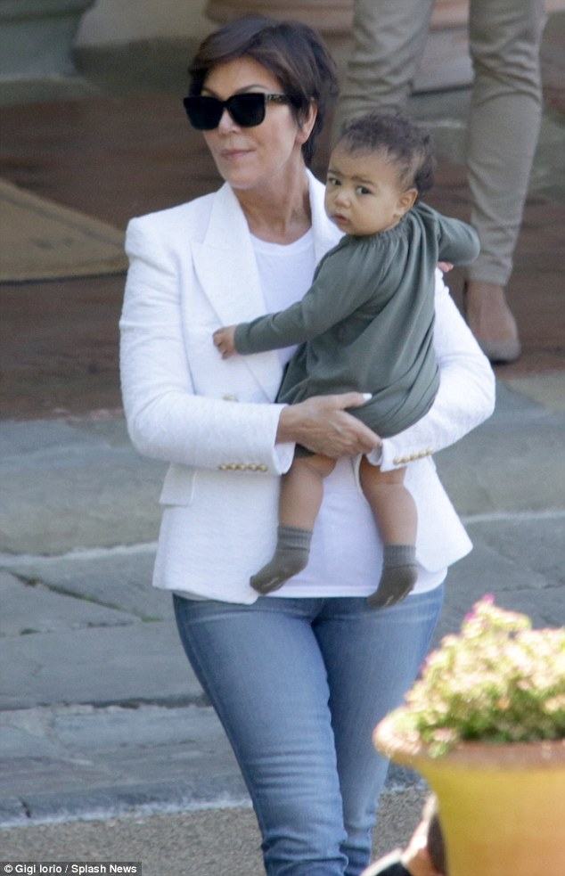 Baby duty: Kris Jenner was seen cradling Kim and Kanye's baby girl North West on Sunday as the family prepared to depart Florence