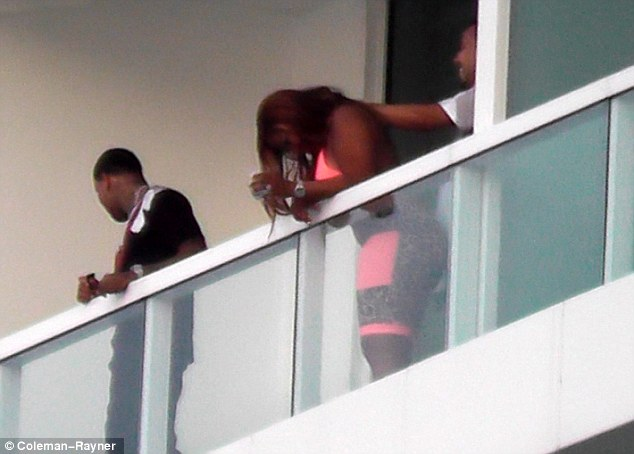 The special treatment: French was then seen giving the woman a neck massage while she leaned over the balcony holding a drink