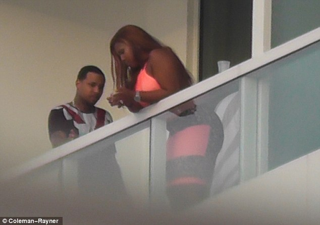 Showing off her assets: The mystery woman wore a skintight neon pink and grey dress for the occasion
