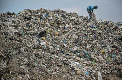 The man searches through a mountain of rubbish to find anything which might make him a buck