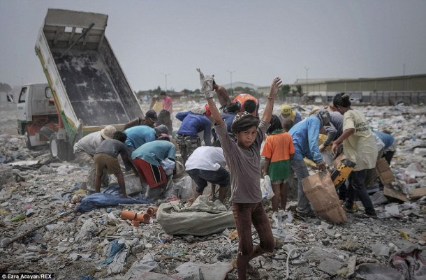 Filipinos look for recyclables at a garbage dump during World Environment Day