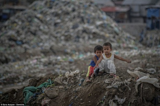 Two boys sit on top of a slope at a garbage dump