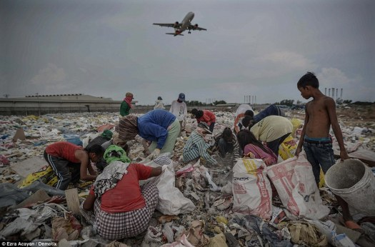 A plane flies overhead as Filipinos look for recyclables at a garbage dump - a sight seen in many countries across the world