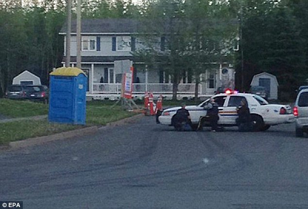 Dramatic: Twitter user Matt Arsenault took this picture of police surrounding a house in Moncton, New Brunswick, after a shootout with suspect Justin Bourque