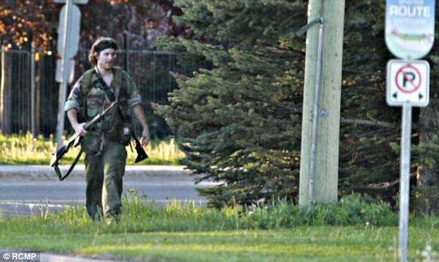 Armed and dangerous: The Royal Canadian Mounted Police tweeted an image of suspected cop killer Justin Bourque, 24, wearing military camouflage and wielding two guns