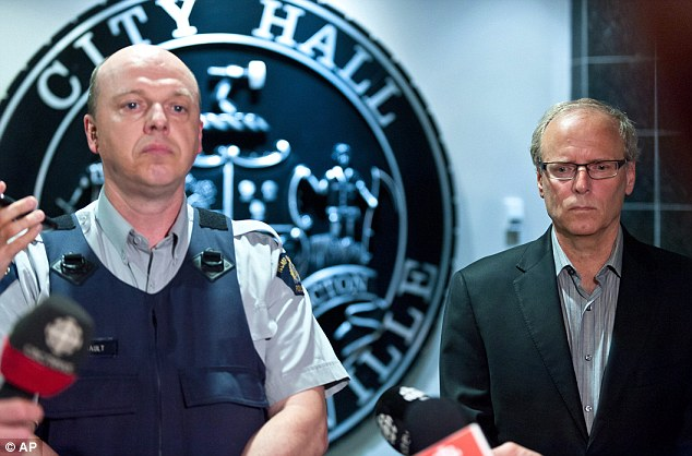 Emotional: Royal Canadian Mounted Police officer Damien Theriault and Mayor George LeBlanc pause to collect themselves before addressing the media during a late night news conference at City Hall in Moncton