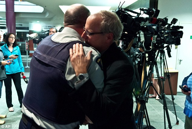 Theriault and Mayor LeBlanc embraced after the emotional news conference about the shootout