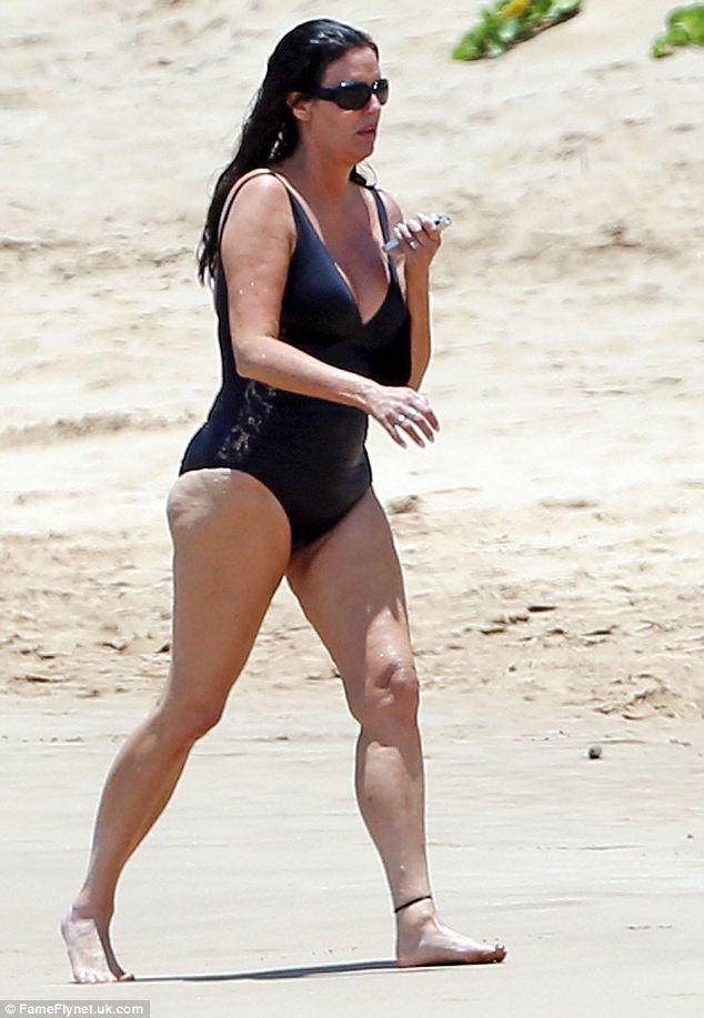Striding out: The dating guru enjoyed a brisk stroll along the beach