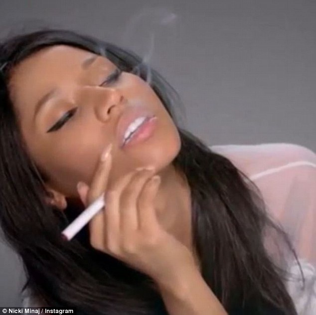 Smoking it up: The 30-year-old is seen puffing on a cigarette at the start of the clip