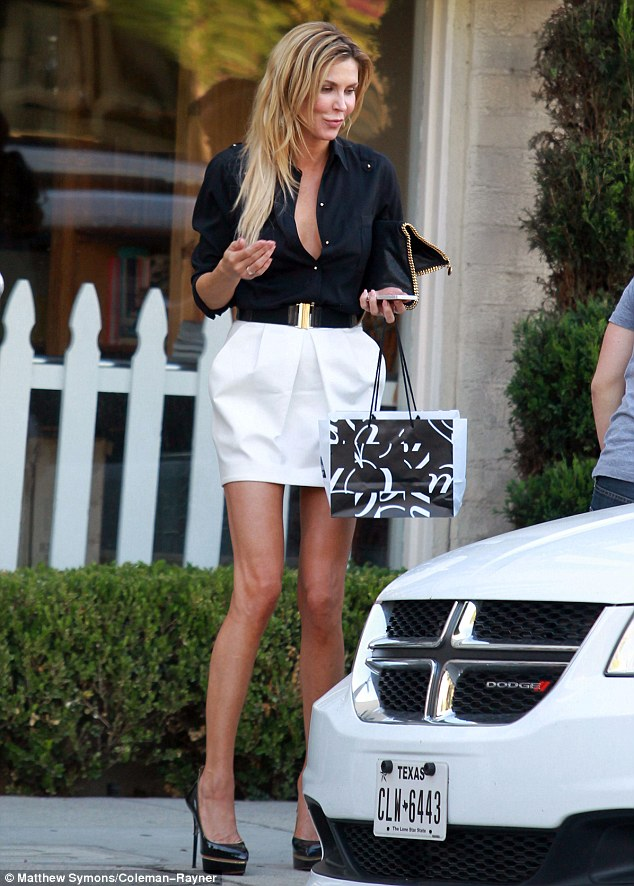 Towering beauty: The leggy blonde displayed her seemingly endless pins in a short white skirt, paired with a black shirt that was unbuttoned low to reveal a hint of cleavage and rolled up at the sleeves, black platform stilettos and a matching clutch with gold zipper trim