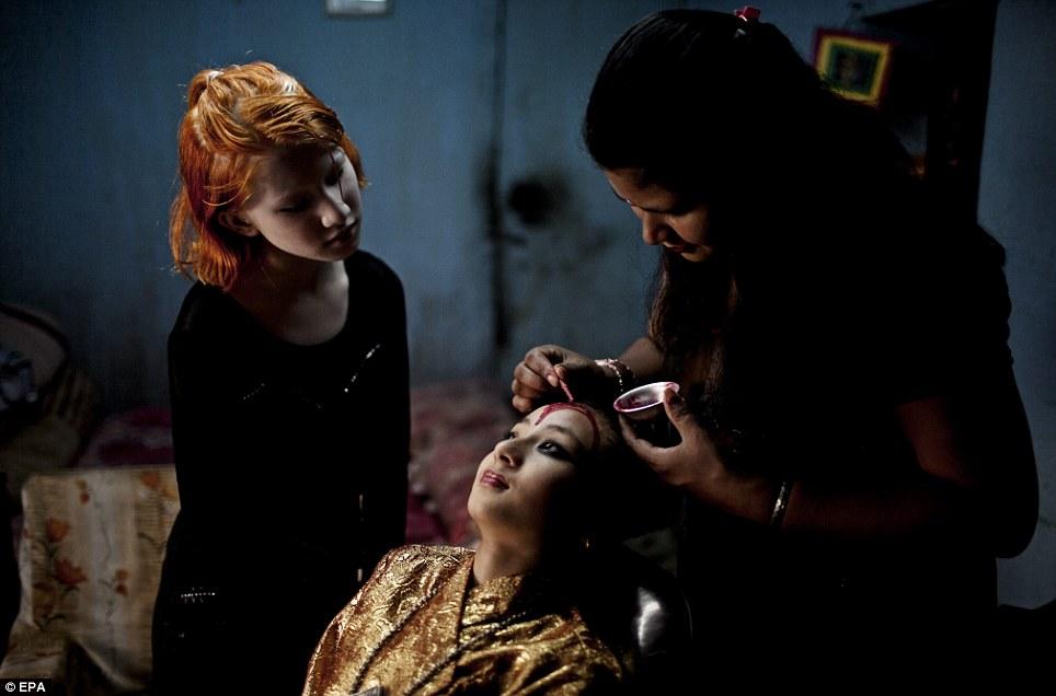 Purna Shova Bajracharya (R), mother of Kumari Samita Bajracharya (C), putting on makeup on her daughter's face for a festival procession at Kumari Ghar in Patan, Nepal