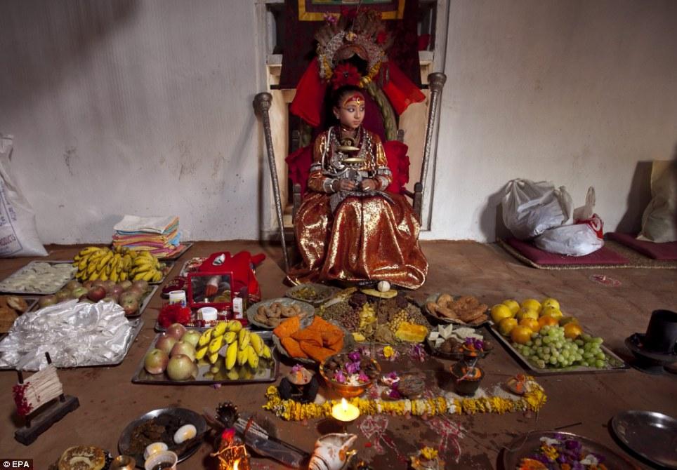 Kumari Samita Bajracharya sits in front of devotees offers during a special puja at Kumari Ghar in Patan, Nepal, 09 April 2011