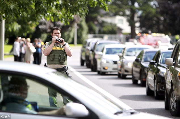 Communication: A sheriff's officer speaks in this radio after a shooting at Reynolds High School Tuesday, June 10, 2014, in Troutdale, Oregon