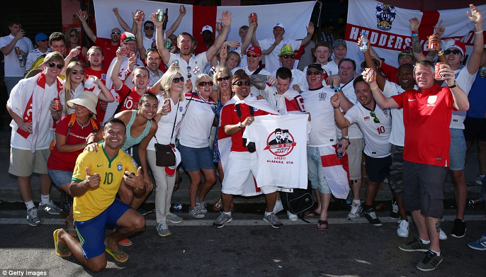 Cheers! Not everyone was imbibing alcohol before the match - this crowd of England fans in Manaus was pictured holding their soft drinks aloft with a Brazilian onlooker