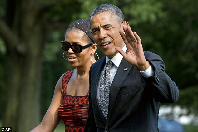 Executive decision to deploy troops: President Barack Obama waves as he walks with first lady Michelle Obama on their return to the White House from a trip to California, on Monday, June 16, 2014, in Washington