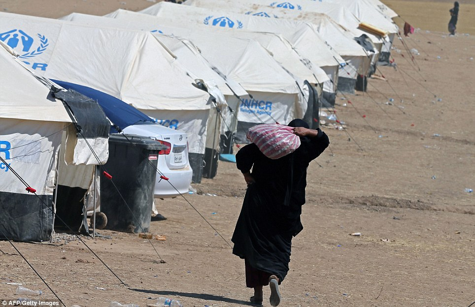 A displaced Iraqi woman walks past tents at a temporary camp set up to shelter Iraqis fleeing violence as militants pushed towards Baghdad
