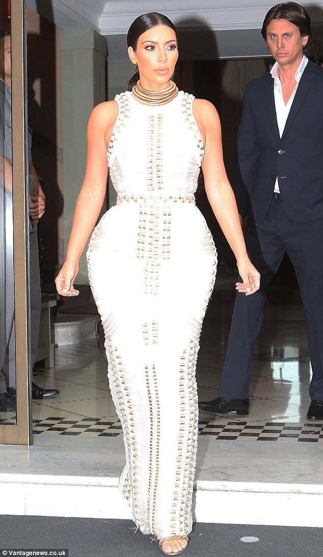 Greek goddess: Kim wowed in a white floor-length gown with rope detailing as she emerged from her hotel