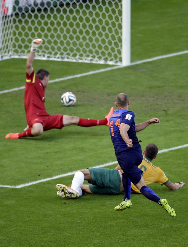 Netherlands' Arjen Robben, front, scores the opening goal past Australia's Matthew Spiranovic, right, and Australia's goalkeeper Mat Ryan, back, during the g...