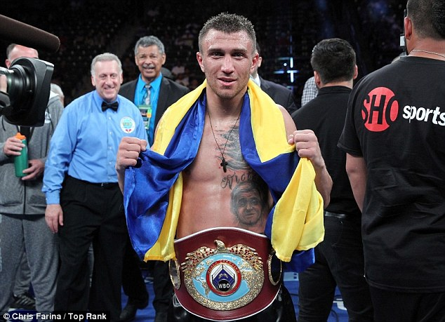 New champion: Vasyl Lomachenko poses with his belt after winning the vacant WBO featherweight title