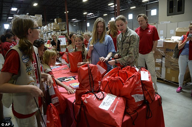 Chelsea, philanthropist, puts a Kits for Kids together with an Air Force cadet at Project C.U.R.E. in Centennial, Colo., on Sunday. The kits are basic supplies to provide parents in developing nations with the supplies  they need for their kids at home