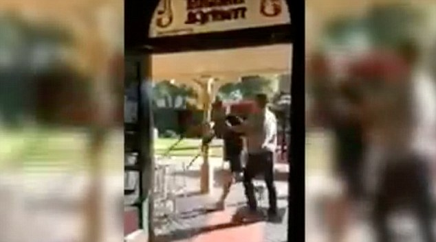 Before he left their attacker picks up a chair and prepares to hurl it through the entrance