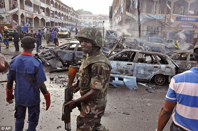 Devastation: A Nigerian soldier at the scene of the explosion which killed 22 people and wounded 17 more in the capital Abuja. Violence is becoming more frequent