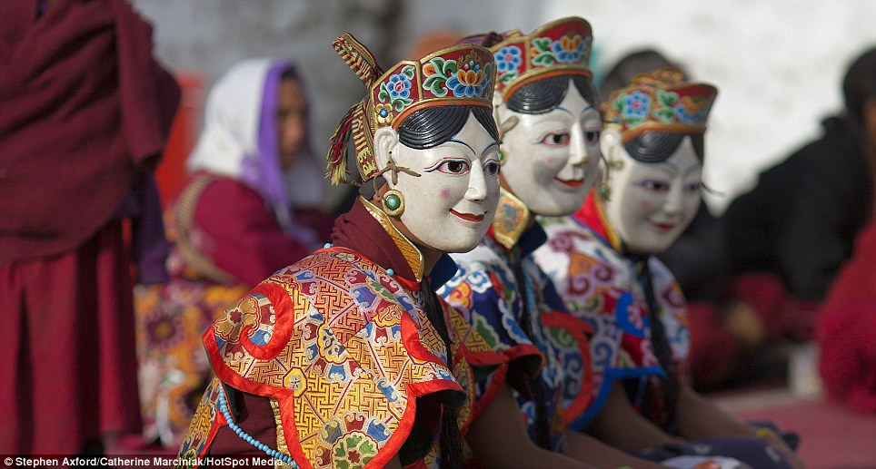 Watching on: Masked performers sit on the edge of the performance ring
